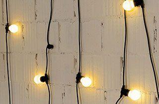 Guirnalda de luces cálidas colgada en pared blanca